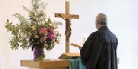 Evangelischer Pfarrer am Altar einer Kirche