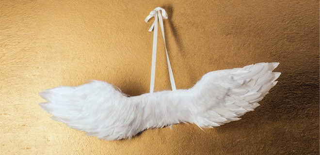Weiße Feder-Flügel zum Anziehen hängen an einem Haken an der Wand