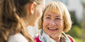 ältere Frau lacht junge Frau an