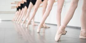 Balletttänzerinnen in schwarzen Trikots trainieren an der Ballettstange