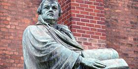 Statue von Martin Luther vor einer Backstein-Kirche